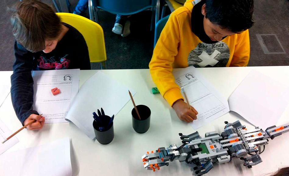 Dos nens montant un robot. Tekhne